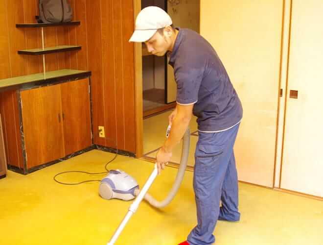 掃除機をかける男性スタッフ