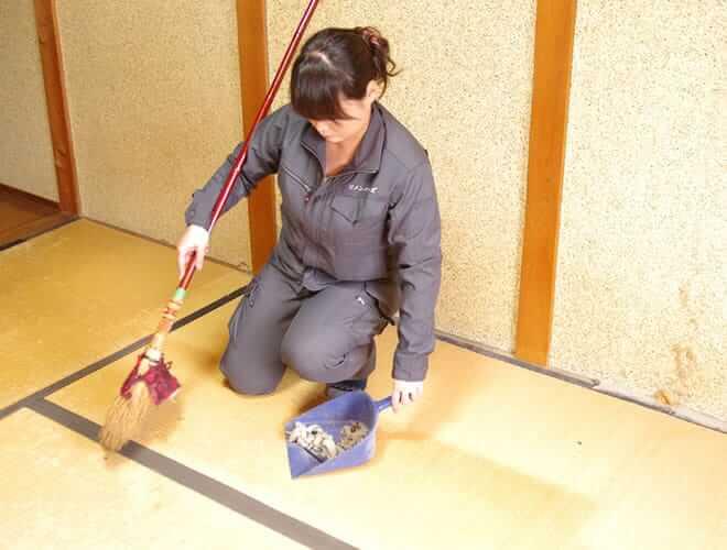 ほうきと塵取りで掃除する女性スタッフ